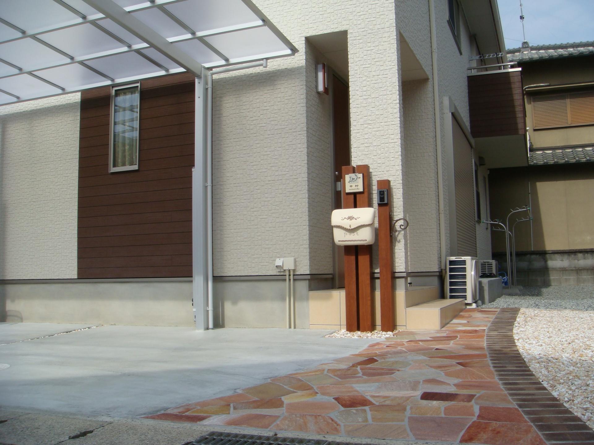 木目調スリット門柱とピンク系乱張りアプローチ