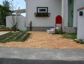 芝生に囲まれた方形アンティークレンガ敷きアプローチ